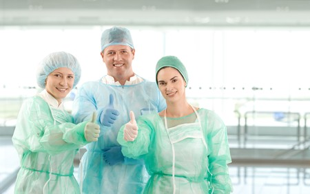 Portrait of successful surgeon team looking at camera on hospital corridor. Copy space on right. photo