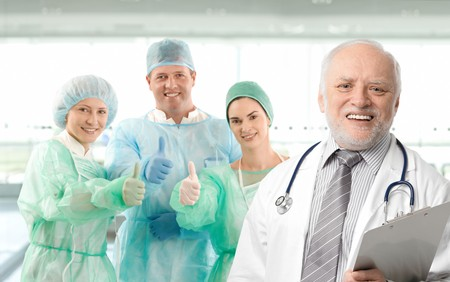 seniority: Surgeon team lead by senior white haired doctor looking at camera, smiling.