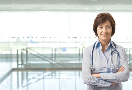 Portrait of senior female doctor on hospital corridor looking at camera smiling. Copy space on left. photo