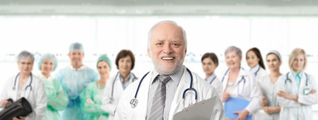 color consultant: Team of medical professionals lead by senior white haired doctor looking at camera, smiling.