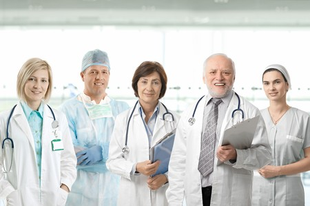 medical physician: Team of medical professionals looking at camera, smiling in hospital lobby. Stock Photo