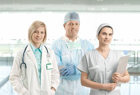 Portrait of smiling medical team of doctor, surgeon and nurse looking at camera on hospital corridor. Stock Photo - 8250776
