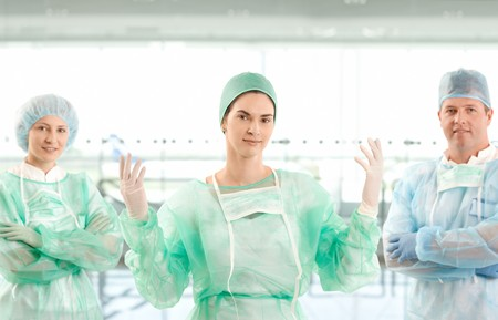 Portrait of smiling surgeon team looking at camera on hospital corridor. photo