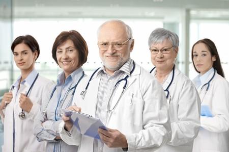 Equipo de profesionales de la medicina de plomo por alto médico de pelo blanco mirando a cámara, sonriendo.