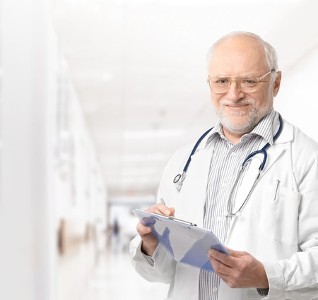 hospital corridor: Portrait of senior doctor on hospital corridor holding clipboard looking at camera smiling. Stock Photo