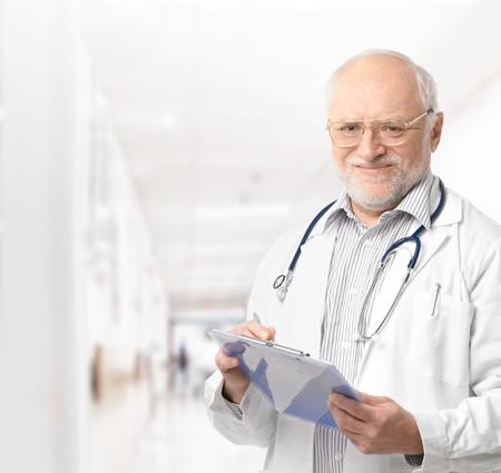 profesor: Retrato de m�dico senior de corredor de hospital celebraci�n de Portapapeles mirando sonriente de la c�mara.