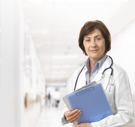 hospital corridor: Portrait of senior female doctor on hospital corridor holding clipboard looking at camera smiling.
