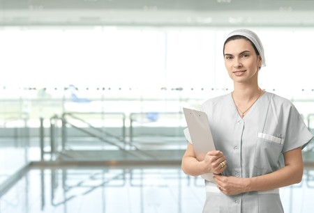 Portrait of attractive female nurse on hospital corridor looking at camera smiling. Copy space on left. photo