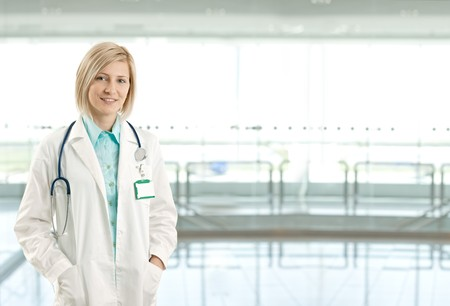 Portrait of attractive female doctor on hospital corridor looking at camera smiling. Copy space on right. Stock Photo - 8250754