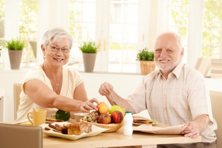 mujeres ancianas: Feliz pareja de ancianos desayunando en cocina, sonriendo a la c�mara.  Foto de archivo