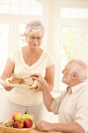 comiendo pan: Sonriente a esposa mayor sirviendo pan para el desayuno a marido sentado a la mesa de la cocina.