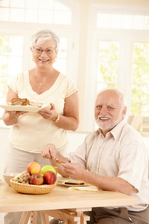 Portrait of happy senior couple at breakfast table in bright kitchen, smiling at camera. photo