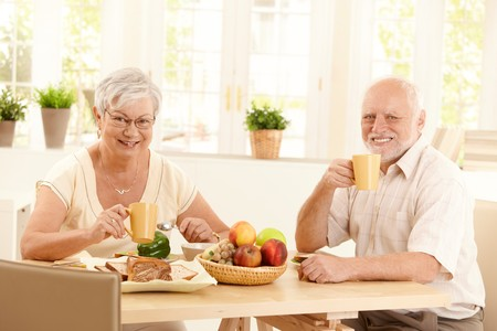 Senior couple having tea at breakfast, sitting in sunny kitchen, smiling. photo