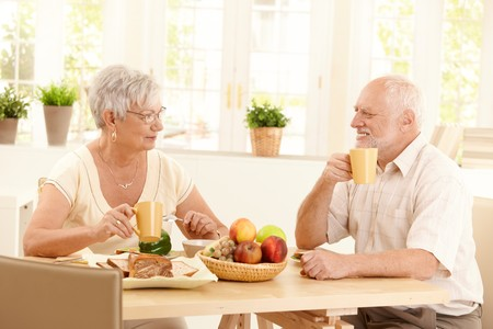 tea cosy: Happy elderly couple having breakfast together at home, smiling, having coffee. Stock Photo