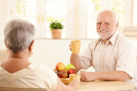 Portrait of happy senior man at breakfast table having tea, sitting with wife. photo