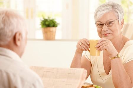 mujeres ancianas: Retrato de mujer senior con caf� de la ma�ana, sonriendo a la c�mara, sentado en la cocina con el marido.