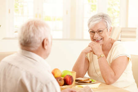 Portrait of happy senior woman sitting at breakfast table, smiling at camera, sitting with husband. photo