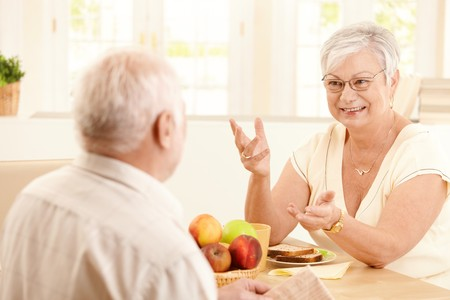Elderly cheerful wife chatting to husband at breakfast table, gesturing, smiling. photo