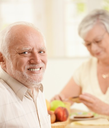 Portrait of happy senior man sitting at breakfast table with wife, smiling at camera. photo