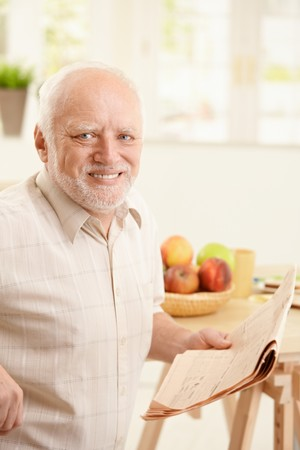 Portrait of happy senior man sitting at breakfast table, holding newspaper, smiling at camera. Stock Photo - 8250818