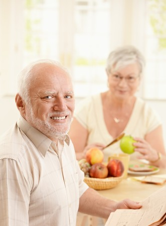 Portrait of smiling older man at kitchen table having breakfast, holding newspaper, with wife in background. photo