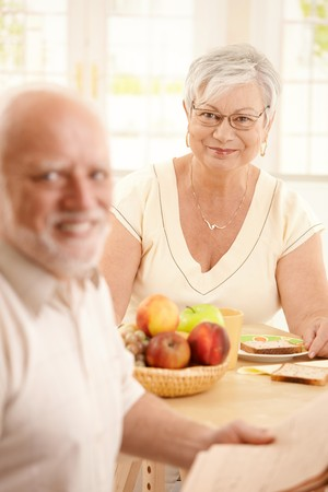 Happy senior woman in focus sitting at kitchen table, having breakfast together with husband, smiling at camera. photo