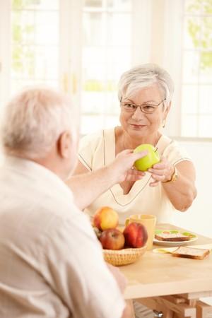 hombre comiendo: Sonriente a esposa anciana entrega manzana verde al marido sobre la mesa de desayuno en la cocina.