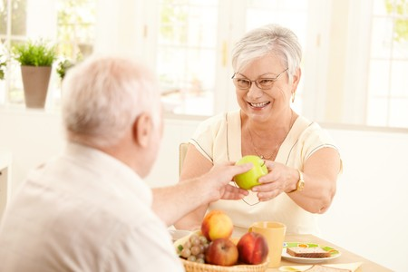 Laughing senior wife getting green apple from husband, sitting at kitchen table, having breakfast. photo