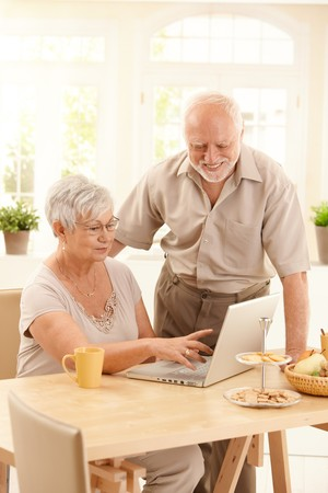 Smiling elderly couple using laptop computer in dining room, smiling, wife pointing at screen. photo