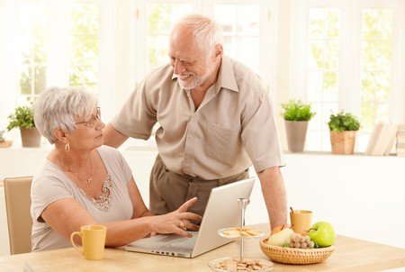 Happy senior couple using laptop computer at home, wife pointing at screen, husband laughing at wife. photo