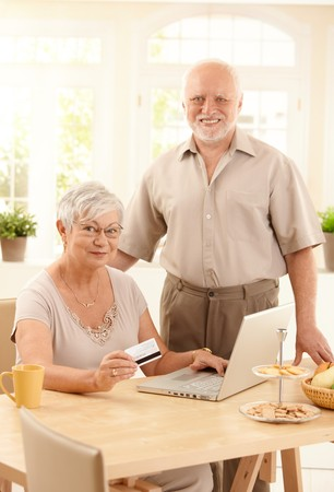 Happy senior couple using laptop computer, purchasing on Internet with credit card at home, smiling at camera. photo