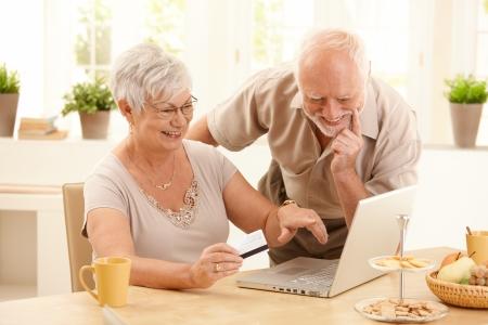 poner atencion: Feliz mayor pareja haciendo compras en l�nea, sonriente esposa apuntando a la pantalla de la computadora port�til.  Foto de archivo