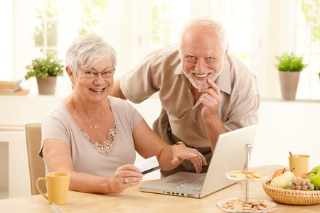 Portrait of happy old couple using credit card and laptop computer to shop online, woman pointing at screen.