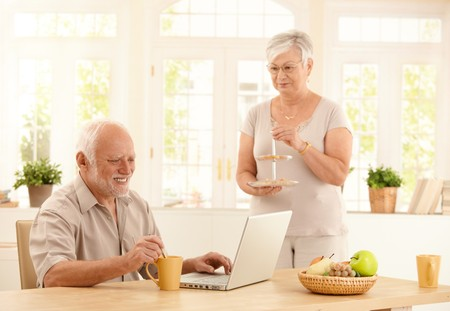 Happy senior man using laptop computer and having coffee at kitchen table, wife serving cookies. photo