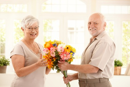 Portrait of happy senior couple with colorful bouquet of flowers, smiling at camera. photo