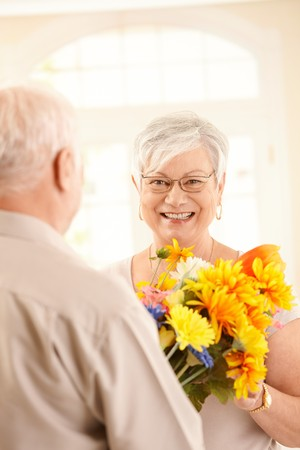 Laughing elderly woman getting flower bouquet, smiling at camera happily. photo