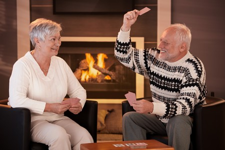 retired couple: Retired couple playing cards in front of fireplace in living room at home, smiling.