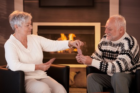 Senior couple playing cards on winter night in front of fireplace. photo