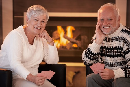 room card: Portrait of happy senior couple playing cards at home in front of cosy fireplace, smiling at camera.