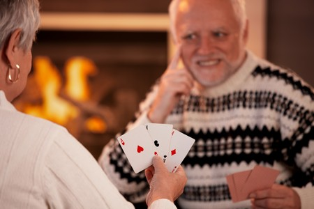 room card: Senior couple playing cards on winter night, cards handheld in focus.