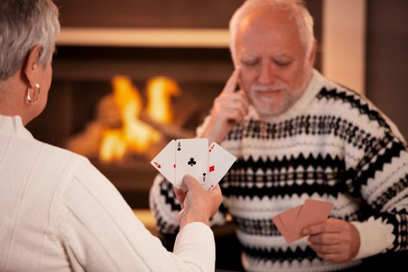 Senior couple playing cards, focus on cards handheld by woman, three ace. photo