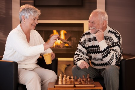 Happy senior couple playing chess at home, drinking tea in front of fireplace, on winter night, laughing. photo