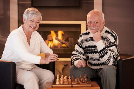 Portrait of elderly couple playing chess at home by fireplace in winter, looking at camera, smiling. photo