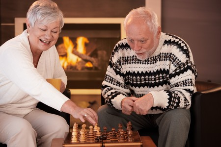 women having fun: Senior couple having fun with chess at home on winter night woman moving chess man on board, man looking surprised.