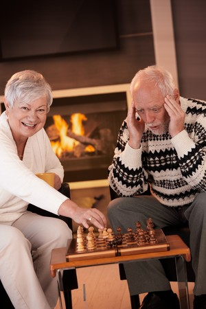 Couple playing chess in cosy living room in front of fireplace, elderly woman winning the game, senior man looking troubled. photo