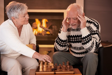 Senior couple playing chess at home, smiling woman winning game, man thinking looking troubled. photo