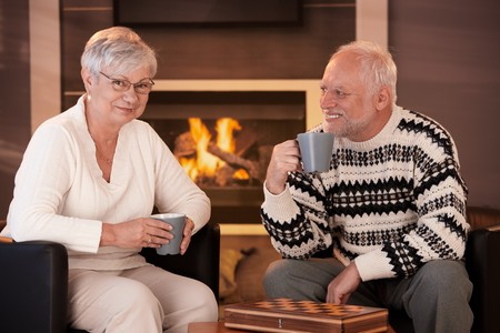 Happy senior couple on winter night at home, sitting in front of fireplace in cosy living room, having tea. photo