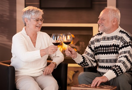 toasting wine: Retired husband and wife drinking red wine together in cosy living room, in front of fireplace, looking happy, smiling. Stock Photo