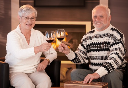 Portrait of senior couple clinking wine glasses, in front of fireplace on winter night, looking at camera happily. Stock Photo - 8250909