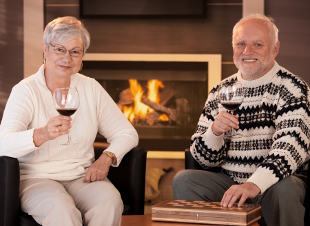 Happy senior couple having wine in front of cosy fireplace at home, smiling at camera. Stock Photo - 8250904